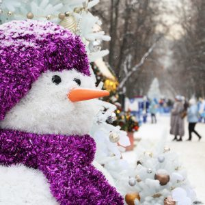 Snowman on a winter street, Christmas decorations in the city. New Year celebration, happy people walking during snowfall