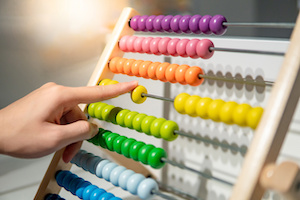 Male hand calculating beads on rainbow abacus