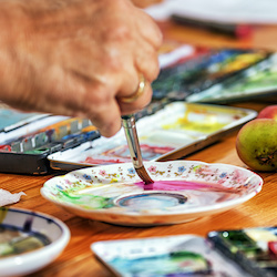 Elderly person painting and doing art activities in an elderly day care centre