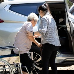 Someone receiving assistance getting in to a vehicle from a wheelchair.