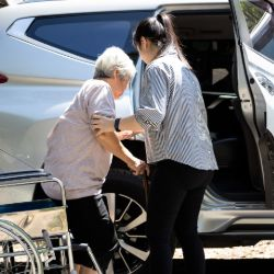 An older person using a voluntary car scheme, being helped by their driver
